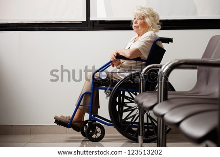 Pensive elderly woman on wheelchair waiting in hospital lobby - stock photo