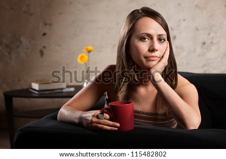 Pensive European woman holding cup with hand on cheek - stock photo
