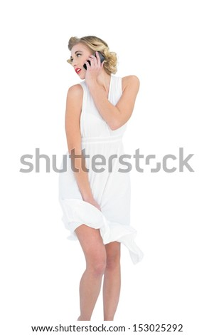 Pensive fashion blonde model calling with her mobile phone on white background - stock photo
