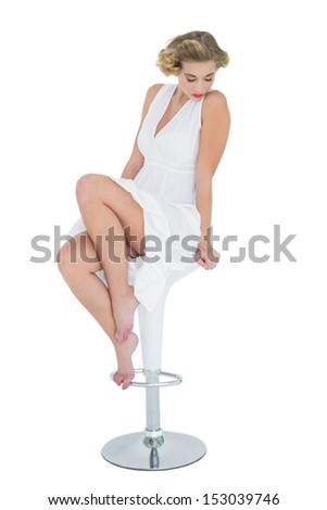 Pensive fashion blonde model posing with closed eyes on bar chair on white background - stock photo