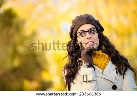 Pensive fashion woman wearing glasses, scarf, wool cap and raincoat in autumn. Cheerful brunette with eyewear thinking or making a decision. - stock photo