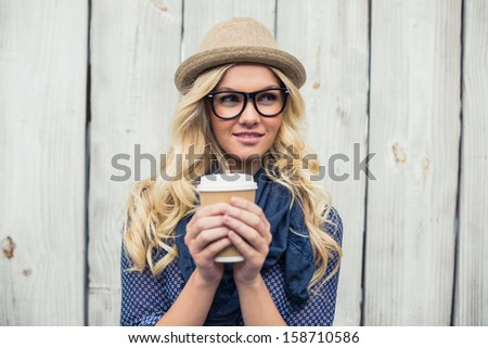Pensive fashionable blonde holding coffee outdoors on wooden background - stock photo