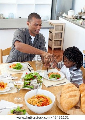 Pensive father and his son have a vegetable dinner in the kitchen - stock photo