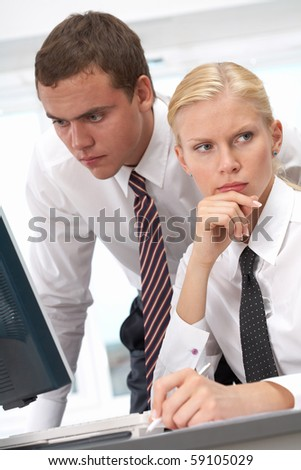 Pensive female looking aside with her boss working near by - stock photo
