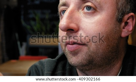 Pensive friendly man emotional close portrait with big expressive eyes significant nose and small stubble beard. Friendly silent reflection thoughtful scene.  - stock photo