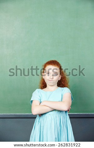 Pensive girl in front of a chalkboard in elementary school - stock photo