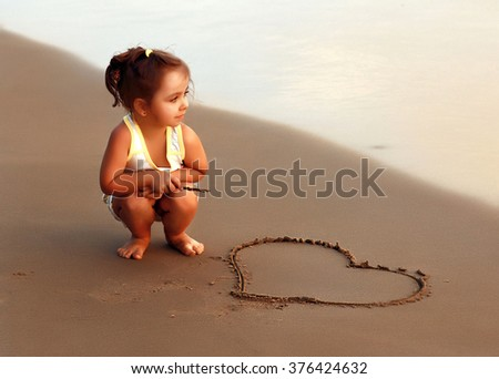 Pensive girl sitting at the evening beach near painted heart and looks into the distance at sea - stock photo