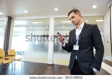 Pensive handsome business man standing in the office and using cell phone  - stock photo