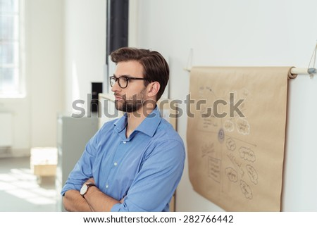 Pensive Handsome Businessman Standing Beside a Poster Paper, with Conceptual Writings, with Arms Crossed and Looking Into the Distance. - stock photo