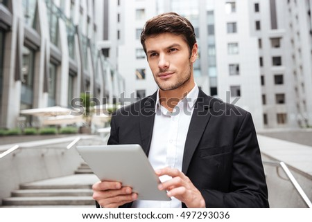 Pensive handsome young businessman using tablet in the city