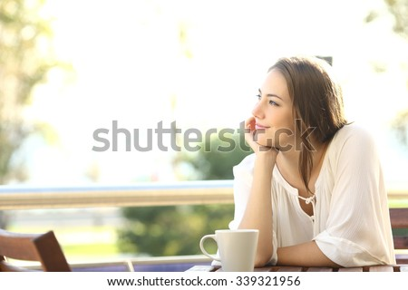 Pensive happy woman remembering looking at side sitting in a bar or home terrace - stock photo