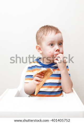 pensive kid smeared with ice cream. child eating chocolate ice cream sitting in a highchair. fingers in the mouth. look towards