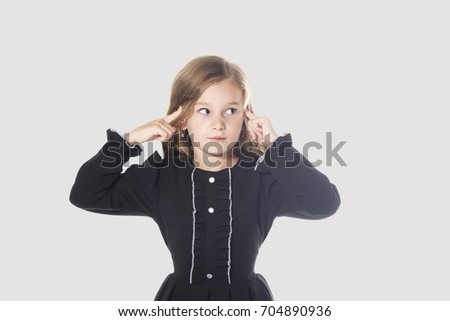 Pensive little girl against grey background. Cute thoughtful kid