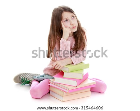 Pensive little girl of school age sitting on the floor leaning on a stack of books. The girl looks in the Top about something dreaming-Isolated on white background - stock photo