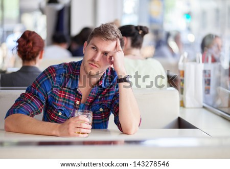 Pensive man drinking beer in a bar - stock photo