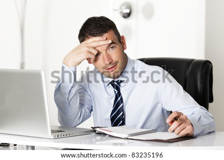 pensive man in office with computer and pen - stock photo