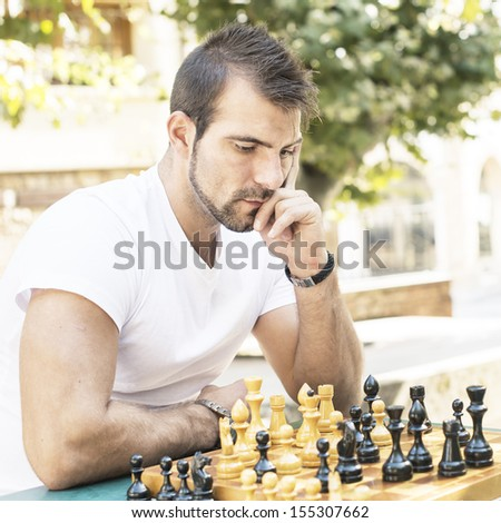 Pensive man plays chess in the park. - stock photo
