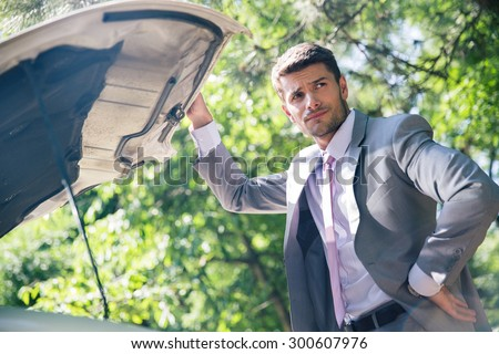 Pensive man standing near breakdown car and looking away - stock photo
