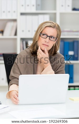 Pensive middle-aged businesswoman wearing glasses sitting at her desk with her hand to her chin staring to the side with a serious thoughtful expression - stock photo