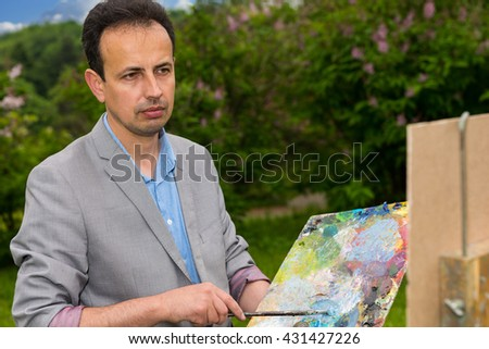Pensive middle-aged painter holding a palette standing in front of a sketchbook during an art class in a forest - stock photo