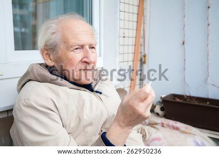 pensive old man enjoying a cigarette - stock photo