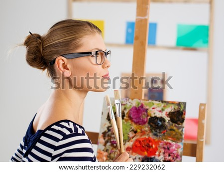 Pensive painter wearing eyeglasses with paintbrushes standing at easel in her artistic studio.  - stock photo