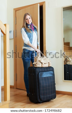 pensive positive woman with suitcase near door at home - stock photo