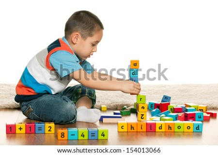 Pensive preschool boy is playing with toys on the floor - stock photo