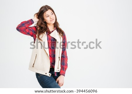 Pensive pretty young woman in plaid shirt and waistcoat standing and touching her hair over white background - stock photo