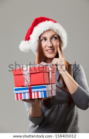 Pensive redhead woman holding Christmas gifts and wearing a Santa hat