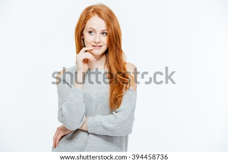 Pensive redhead woman standing isolated on a white background - stock photo