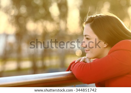 Pensive relaxed girl thinking in winter looking forward at sunset - stock photo