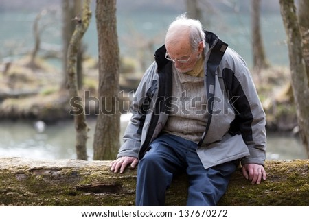 Pensive senior man sitting on tree trunk in nature - stock photo