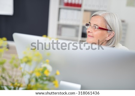 Pensive Senior Office Woman Looking Into the Distance While Sitting at her Table. - stock photo