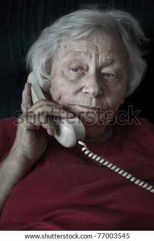 Pensive senior woman talking on the phone - stock photo