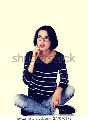 Pensive student sitting cross-legged on the floor. - stock photo