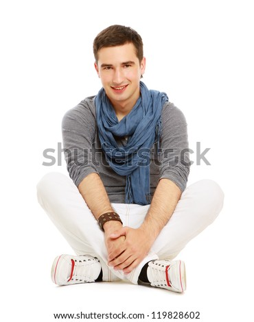 Pensive stylish young man sitting on floor and looking at camera,isolated on white background - stock photo