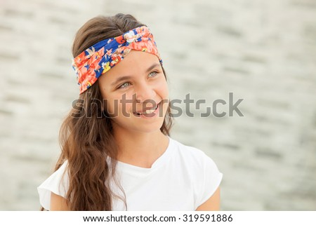 Pensive teenager girl with a flowered headband smiling outside - stock photo