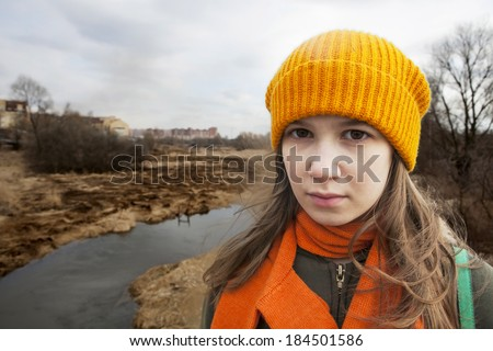 Pensive Teenager in orange knitte? hat and scarf stand alone near the scorched field. Spring time - stock photo