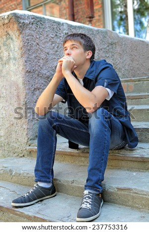 Pensive Teenager on the landing steps of the House - stock photo