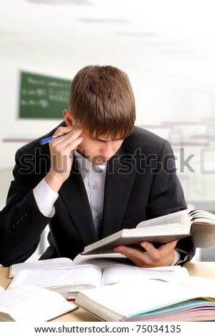 pensive teenager sitting in the classroom - stock photo