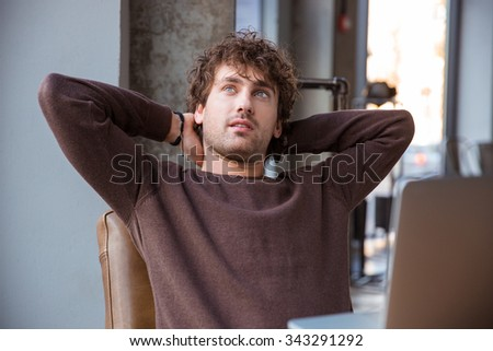 Pensive thoughtful dreaming curly attractive handsome man in brown sweetshirt holding hands behind head while sitting at his working place - stock photo