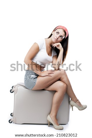 Pensive tourist woman with suitcase isolated white - stock photo
