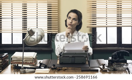 Pensive vintage woman with hand on chin, typing on typewriter and looking for inspiration - stock photo