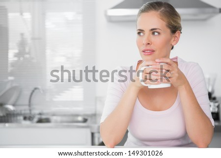Pensive woman having coffee in her kitchen - stock photo
