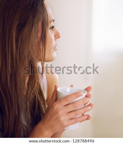 Pensive woman  in a quiet mood thinking of something over a cup of coffee - stock photo