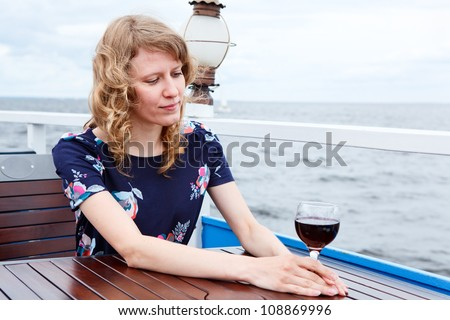 Pensive woman in dress with wine glass sitting at the table - stock photo