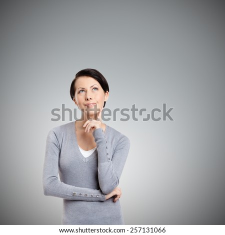 Pensive woman, isolated on grey background - stock photo