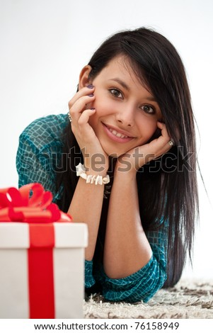 Pensive woman lying on the floor and smiling with gift box
