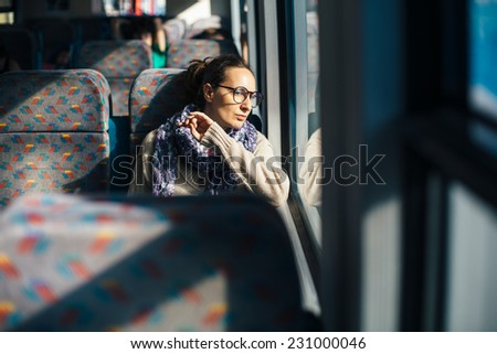 Pensive woman traveling by bus train - stock photo